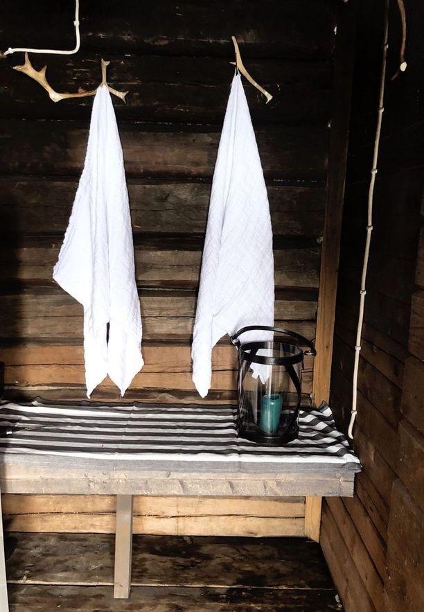 Satavuotiaan saunarakennuksen eteisessä on poronsarvinaulakot. Pellavapyyhkeet ja lyhdyn Maiju on ostanut Oulun Balmuirilta.