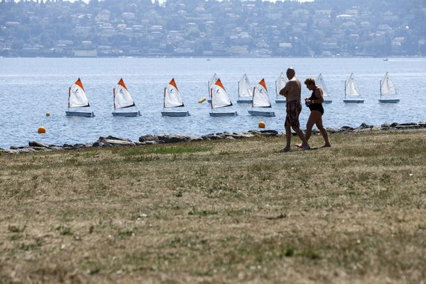 Kuvassa henkilöt vilvoittelevat Genevenjärven rannalla Sveitsissä 3. elokuuta 2018.