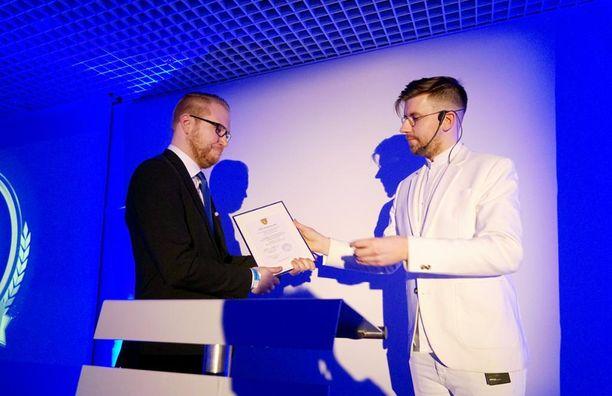 Perussuomalaisten nuorten nykyinen puheenjohtaja Sebastian Tynkkynen ojensi ansiomerkin kansanedustaja Olli Immoselle.