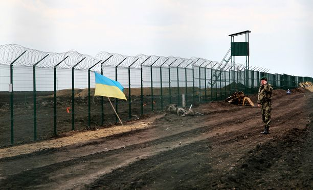 Huhtikuussa otetussa kuvassa ukrainalainen rajavartija puhuu puhelimessa Ukrainan ja Venäjän välisellä rajalla Harkovan lähistöllä.