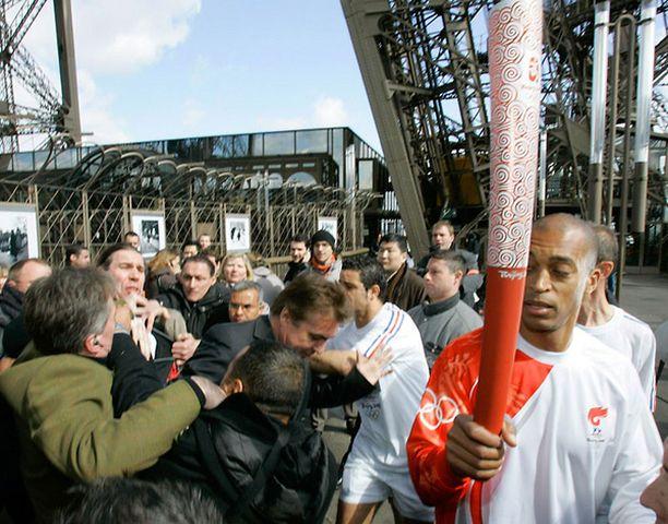 Turvamiehet taltuttavat mielenosoittajia Pariisin Eiffel-tornin juurella. Soihtua kantaa Stephane Diagana, 400 metrin juoksun maailmanmestari vuodelta 1997.
