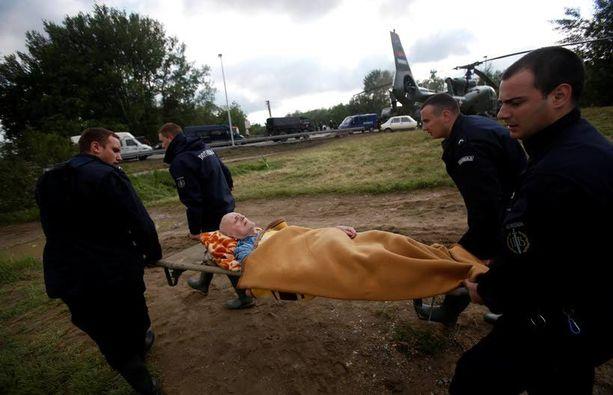 Serbian poliisit kantoivat paareilla miestä, jota evakuoitiin sotilashelikopteriin Obrenovacin kaupungista Serbiassa.