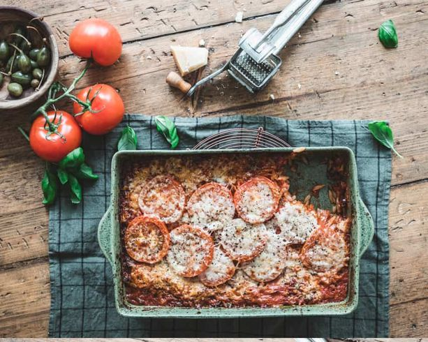 Paiston loppuvaiheessa pasta puttanescan päälle asetellaan tomaattisiivut ja juustoraaste.