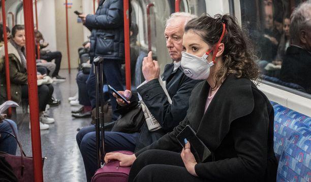 Lontoon metrossa nainen on suojautunut naamarilla.