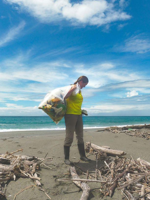 Maria Ojajärvi muoviroskaa keräämässä. Työ on arvokasta, sillä kilpikonnanaaraat eivät välttämättä pääse munimaan rannalle muoviroskan takia eivätkä poikaset pääse mereen