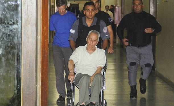 Nicola Corradi on kytketty pöyrätuoliin käsiraudoilla. Takana vasemmalla kävelee Horacio Corbacho.