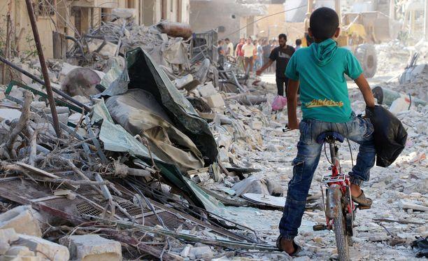 Ihmiset etsivät eloonjääneitä Idlibin provinssin Armanazissa ilmaiskun jälkeen lauantaina. Ainakin 33 ihmistä kuoli iskussa.