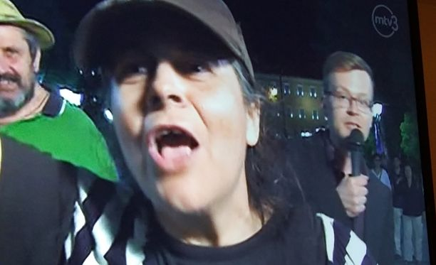 Kreikkalainen nainen tunki myöhäisuutisten suoraan lähetykseen. Taustalla toimittaja yrittää raportoida välikohtauksesta huolimatta.