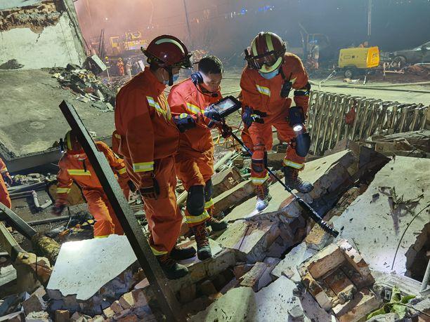 Pelastajat tutkivat nestekaasurekan räjähdyksen seurauksena tuhoutuneen rakennuksen raunioita.