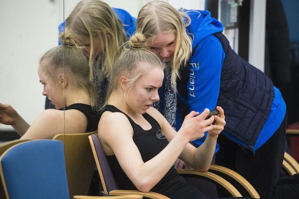 Rytminen voimistelija Jouki Tikkanen katsoo suoritusta kännykästä valmentaja Titta Heikkilän kanssa. Urheilulehden haastattelussa Tikkanen sanoo, että Heikkilä ei ole koskaan kohdellut häntä epäinhimillisesti.