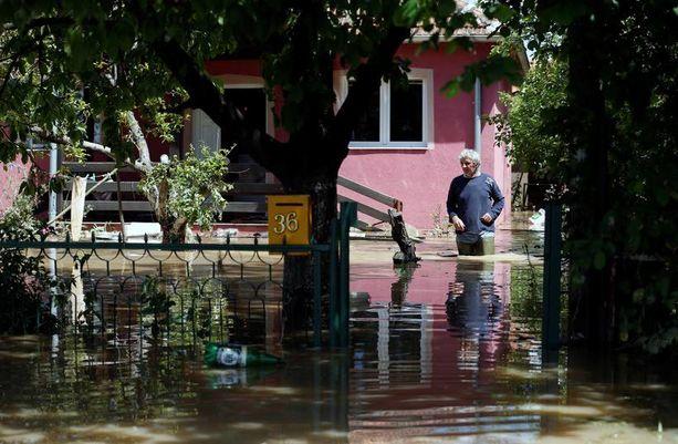Mies käveli tulvien varassa olevan kotitalonsa edessä Serbiassa, jonne on yhä odotettavissa lisää sateita.