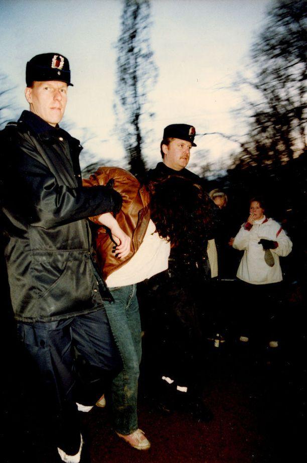 Poliisit taluttivat väsynyttä juhlijaa Helsingissä vappuna 1995.