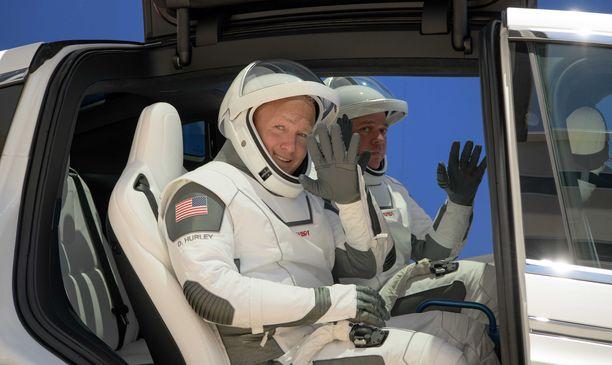 Doug Hurley (vas.) ja Bob Behnken vilkuttavat iloisesti SpaceX-univormuissaan.
