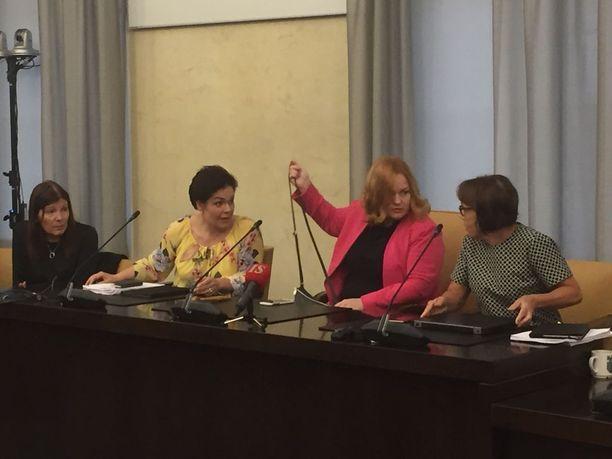 Keskellä (käsi pystyssä) sosiaali- ja terveysvaliokunnan puheenjohtaja Krista Kiuru (sd), hänestä vasemmalle varapuheenjohtaja Hannakaisa Heikkinen ja Sari Sarkomaa (kok).