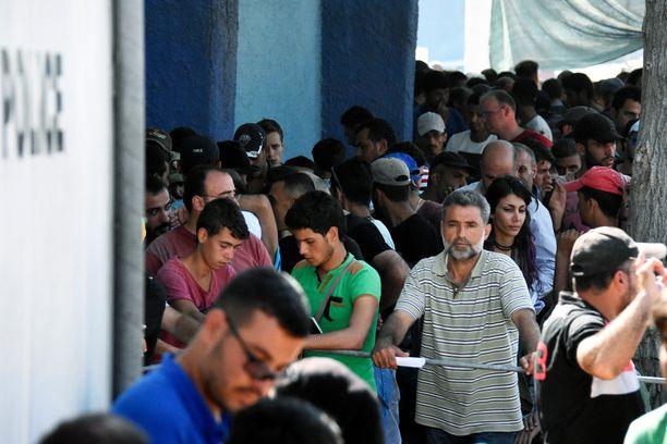 Pakolaiset jonottavat poliisikontille päästäkseen rekisteröitymään ja jatkamaan matkaansa.