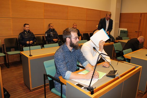 Murhasta syytetty mies peitti kasvonsa oikeussalissa. Syytetyn vieressä istuu tämän asianajaja Mikko Marttila.