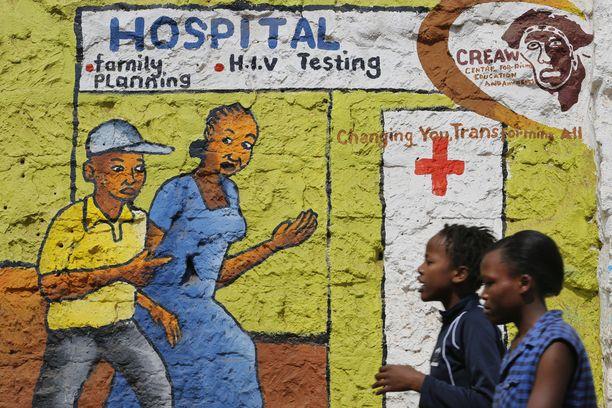 Naiset ohittivat hivistä ja aidsista tiedottavan seinämaalauksen Kiberan slummissa Kenian Nairobissa. Kuvituskuva.