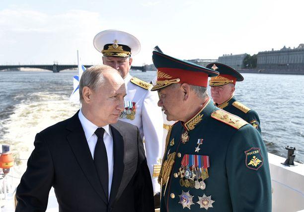 Venäjän presidentti Vladimir Putin keskustelee puolustusministeri Sergei Shoigun kanssa merivoimien laivastoparaatin yhteydessä Pietarissa.