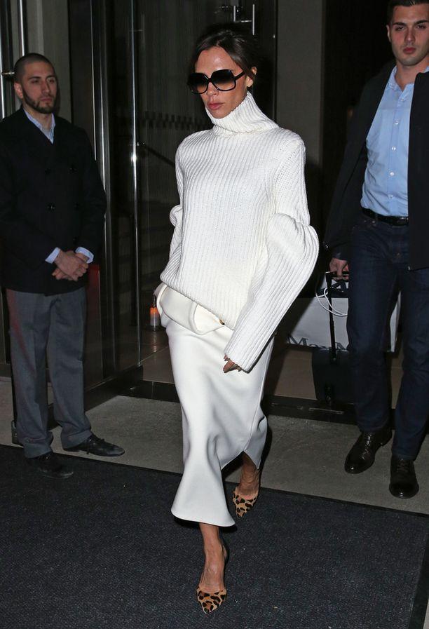 Victoria Beckham antaa ison neuleen roikkua muodikkaasti hameen päällä. Huomaa myös vyölaukku - valkoinen totta kai.