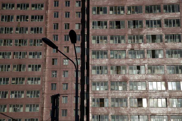 Ilta-aurinko heijastuu massiivisen asuinrakennuksen ikkunoista.