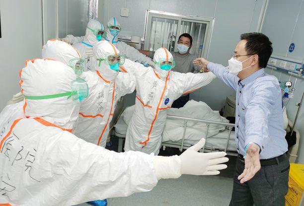 Koronaviruksen selättänyt wuhanilaismies kiittää sairaalan hoitohenkilökuntaa halaamalla heitä välimatkan päästä.