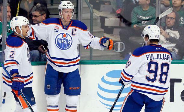 Andrej Sekera ja Jesse Puljujärvi rientävät onnittelemaan maalin tehnyttä Connor McDavidia.