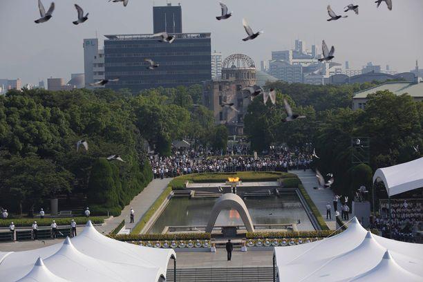 Kyyhkyset lensivät ohi kesken Hiroshimassa Rauhanpuistossa järjestetyn muistotilaisuuden