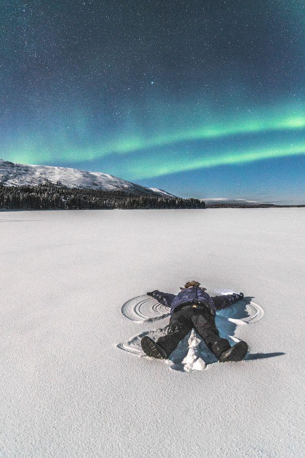 Retkeilijä lumienkeleitä tekemässä Pallasjärven jäällä.