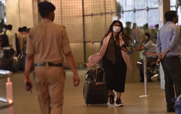 Intian Mumbaissa lentokentän matkustajille annetaan leimoja, joissa kerrotaan määräyksestä karanteeniin.