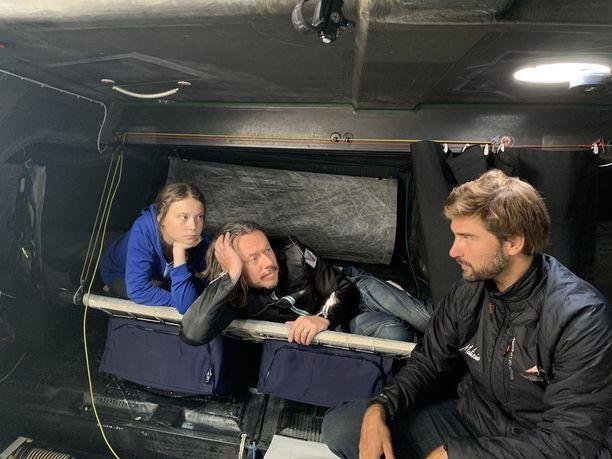 Greta Thunberg, hänen isänsä Svante Thunberg ja laivan kapteeni Boris Herrmann sisällä Malizia II -kilpapurjeveneessä, jolla noin kaksi viikkoa kestävä Atlantin ylitys tehdään.