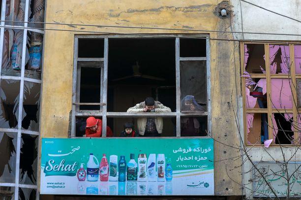Perhe katselee asunnon ikkunasta räjähdyksen jälkiä Kabulissa, Afganistanissa helmikuussa 2021.