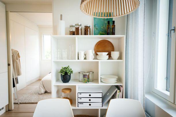 Keittiön pöydän takana on hylly, jossa on esimerkiksi papereiden arkistointilokerikko.