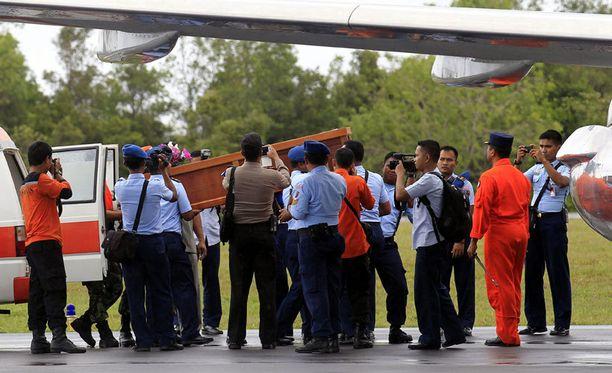 Pelastustyöntekijät nostavat ruumisarkkua koneeseen.