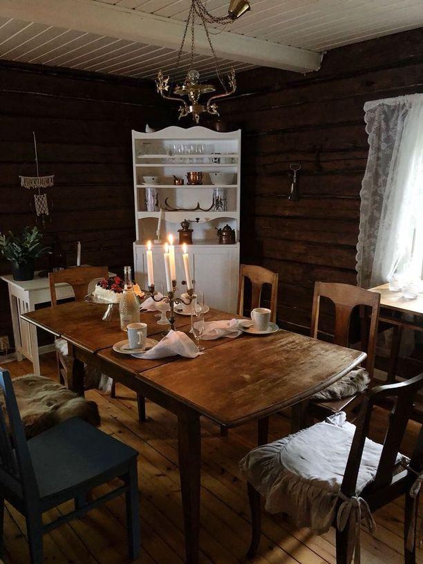 Vanha pöytä ja tuolit sopivat hirsimökin tyyliin. Kaappi on maalattu valkoiseksi remontin yhteydessä ja Balmuirin pellavaiset lautasliinat kruunaavat kahvipöydän kattauksen.