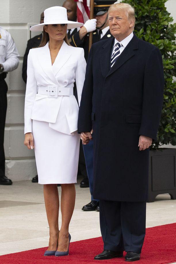 Donald Trumpin valtaannousu oli varsinainen hattutemppu, mutta sellainen on myös tämä Melanien asu, jossa hän tapasi Ranskan presidenttiparin huhtikuussa 2018. Tyyli on huoliteltu ja viimeisen päälle, mutta valtava hattu peittää hassusti naisen kasvot. Bleiseri, vyö, hame ja hattu ovat kaikki Michael Korsin käsialaa.