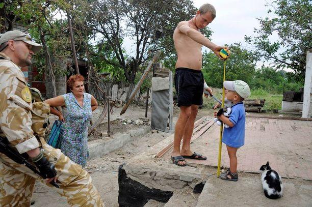Siviili-sotilas yhteistyön keskus CIMIC lupaa toimittaa Andriivkan kylään ruoan lisäksi myös vaatteita. Aleksei mittaa 2-vuotiaan Leonidin vaatekokoa varten.