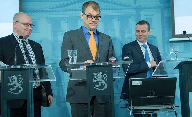 Työ- ja oikeusministeri Jari Lindström (vas.), pääministeri Juha Sipilä (kesk) ja valtiovarainministeri Petteri Orpo (kok) tiedotustilaisuudessa.