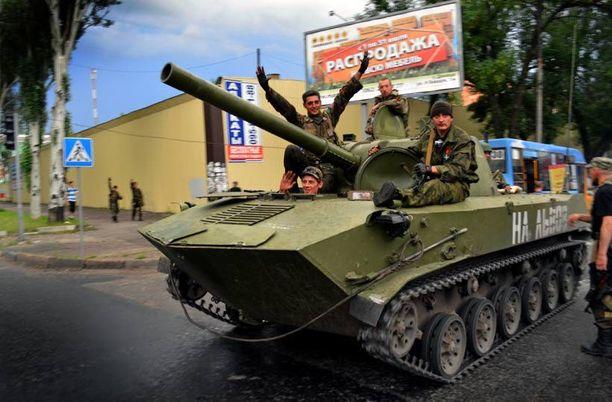 Separatistitaistelijat juhlivat Donetskin keskustassa Ukrainan armeijalta varastetuilla panssarivaunuilla ajellen.