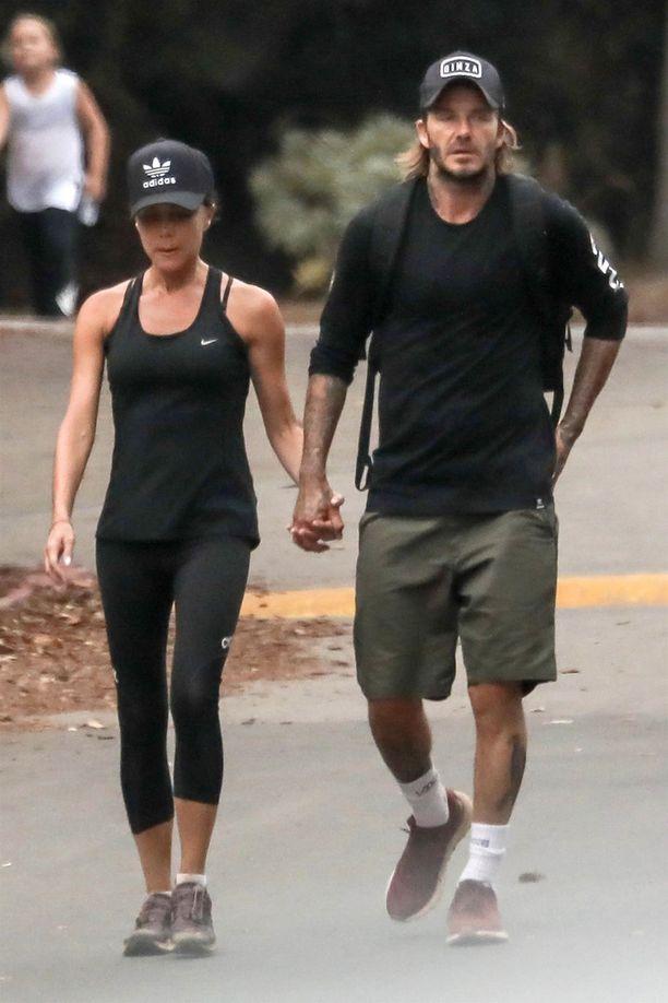 Victoria ja David Beckham palaavat treeneistä käsi kädessä, silti ilmeet ovat kovin vakavat.