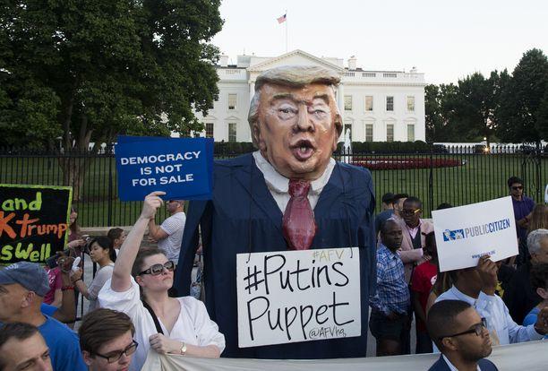 """Helsingin huippukokous sai mielenosoittajat koolle Washingtonissa. Trumpia kutsuttiin """"Putinin sätkynukeksi"""" ja hänen viraltapanoaan vaadittiin."""