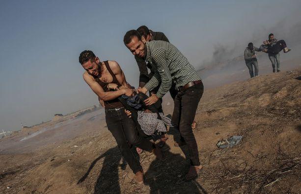 Palestiinalaiset kantoivat haavoittunutta naismielenosoittajaa Gazan kaistaleella. Ainakin 60 ihmistä kuoli ja 2 500 haavoittui maanantaina Gazan ja Israelin rajalla.