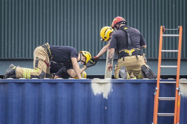 Palomiehet tarkistavat auki sahatun kontin sisältöä Länsiterminaalissa tiistaina 20. heinäkuuta.