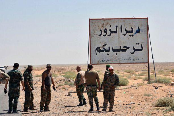 """Syyrian virallisen uutistoimiston Sanan sunnuntaina julkaisemassa kuvassa Syyrian hallituksen joukot seisovat """"Tervetuloa Deir ez-Zoriin"""" -kyltin vieressä."""