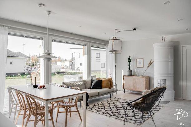 Skandinaavisessa kodissa kannattaa suosia luonnonvaloa ja antaa isojen ikkunoiden tehdä tehtävänsä. Ruokapöydän päällä on Poul Henningsenin suunnittelema PH5- ja olohuoneessa Ay Illuminate -valaisin.