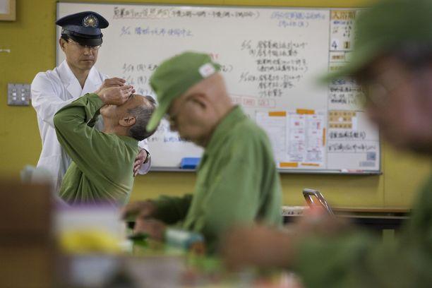 Vankilan sairaanhoitaja katsoo, kun vanhempi vanki laittaa silmätippoja.