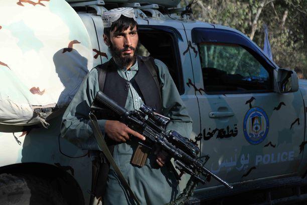 Talebanin taistelija poseeraan afganistanilaisen poliisiauton vieressä. Talebanin taistelijat ovat saaneet armeijalta ja poliisilta paljon modernia aseistusta.