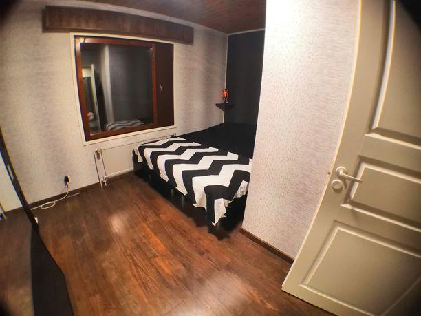 Uudessa makuuhuoneessa on tyylikäs pähkinälaminaattilattia sekä tumma tehosteseinä.