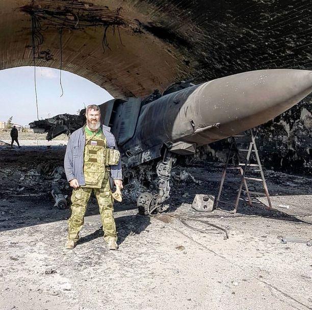 Venäläinen näyttelijä Sergei Badjuk poseerasi Yhdysvaltain risteilyohjusiskussa tuhoutuneen neuvostoaikaisen Mig-23 -koneen jäänteiden edessä. Badjuk julkaisi tämän kuvan Instagram-tilillään tehtyään paikan päältä Shayratin lentotukikohdasta videoraportin venäläiselle tv-kanavalle viime lauantaina.