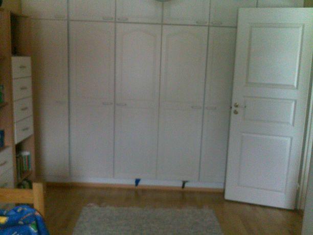 Toisella seinällä huonetta rajoittaa ovi, sekä kaapisto.