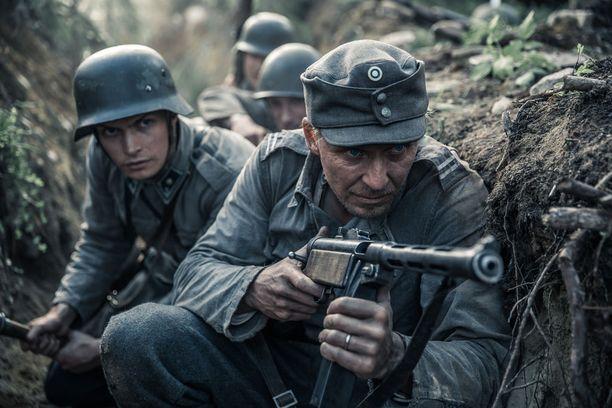 Antti Rokka (Eero Aho) kantaa sodan kauhuja harteillaan. Taustalla väijyy Kariluoto (Johannes Holopainen).